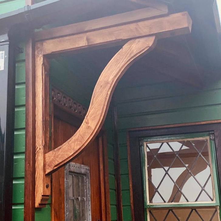 Snake style gallows bracket with a dark stain, used as a decorative feature on an outbuilding painted in a mid shade of green.