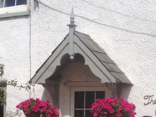 Filcombe door canopy finished in grey with pink flowers in hanging baskets either side